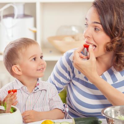 Mãe e filho a comer tomate